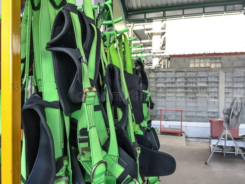 Voller Auffanggurt, der am Gestell, persönliche Schutzausrüstung für Höhenarbeit hängt stockbild