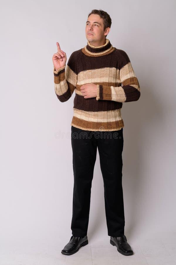 Voller Körperschuß des gut aussehenden Mannes bereites zum Winter oben denkend und zeigend lizenzfreie stockfotografie