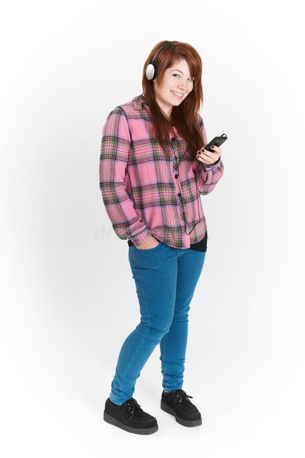 In voller Länge herausgeschnitten von der Jugendlichen, die auf MP3-Player hört stockfotografie