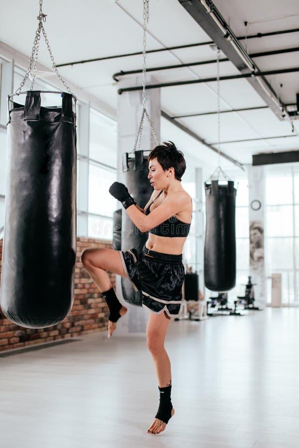 In voller Länge vom Athleten, der auf Kickboxenposition mit dem verbogenen Bein steht lizenzfreies stockbild