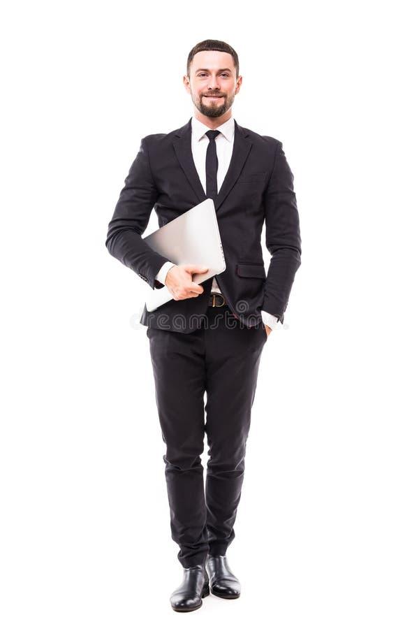 In voller Länge vom attraktiven jungen Geschäftsmann, der Laptop über weißem Hintergrund geht und hält lizenzfreie stockbilder