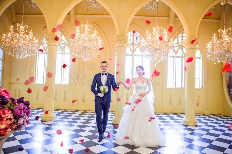 In voller Länge vom eleganten Hochzeitspaarhändchenhalten in der Kirche stockfotos
