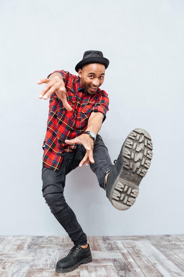 In voller Länge vom frohen afrikanischen lächelnden und tanzenden Mann lizenzfreie stockbilder