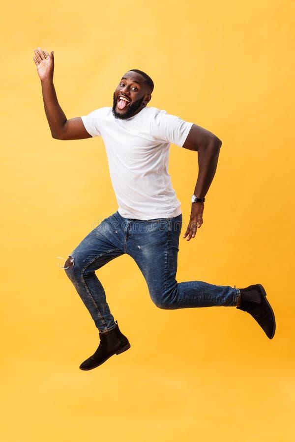 In voller Länge vom hübschen jungen schwarzen Mann, der gegen gelben Hintergrund springt lizenzfreies stockfoto