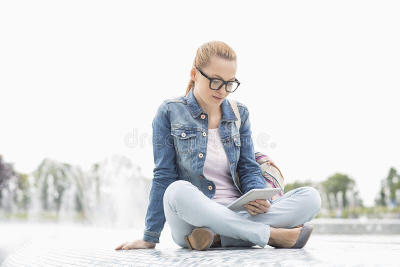 In voller Länge vom jungen weiblichen Studenten, der digitale Tablette im Park verwendet lizenzfreie stockfotos