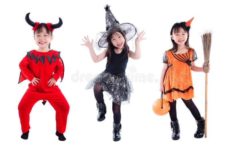 In voller Länge vom Mädchen, das Halloween-Kostümstellung über Weiß trägt stockfotos