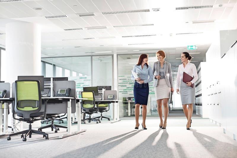 In voller Länge von den Geschäftsfrauen mit Dateiordnern gehend in Büro stockfoto