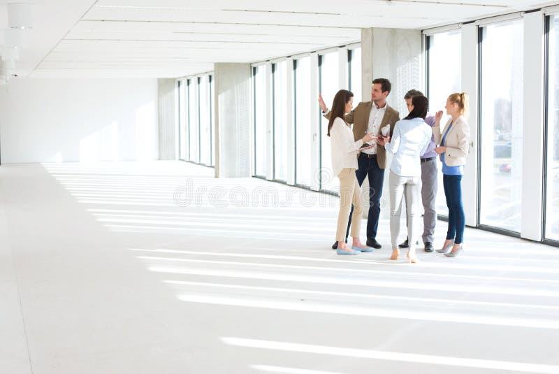 In voller Länge von den Geschäftsleuten, die Diskussion in den leeren Büroräumen haben stockfotografie
