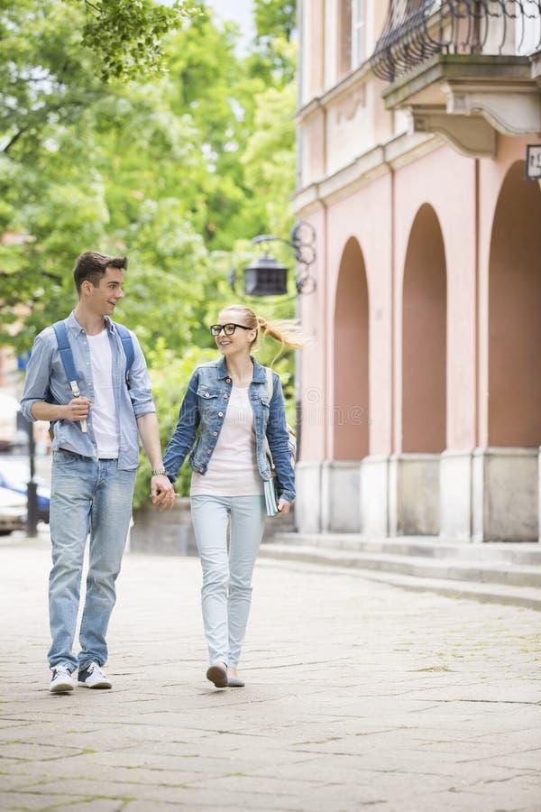 In voller Länge von den jungen sprechenden Collegepaaren beim Gehen in Campus lizenzfreie stockfotografie