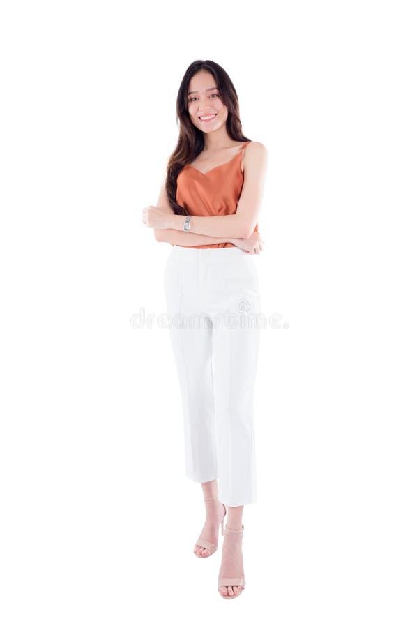In voller Länge von der Frau, die an der Kamera lokalisiert über weißem Hintergrund lächelt lizenzfreies stockfoto