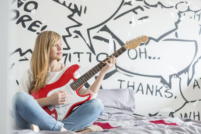 In voller Länge von der Jugendlichen, die Gitarre im Schlafzimmer spielt lizenzfreie stockfotos