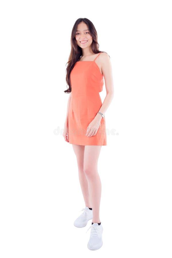 In voller Länge von der jungen Frau, die an der Kamera lokalisiert über weißem Hintergrund lächelt lizenzfreies stockbild