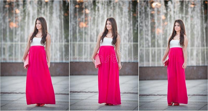In voller Länge von der jungen kaukasischen Frau mit dem langen roten Rock, der nahen Brunnen steht lizenzfreie stockfotos