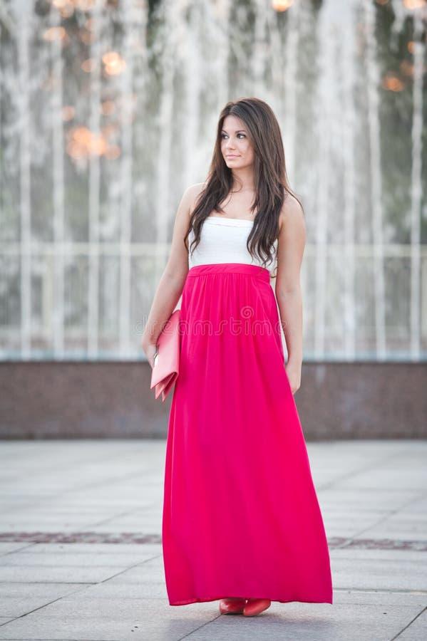 In voller Länge von der jungen kaukasischen Frau mit dem langen roten Rock, der vor einem Brunnen im Freien steht stockfotografie