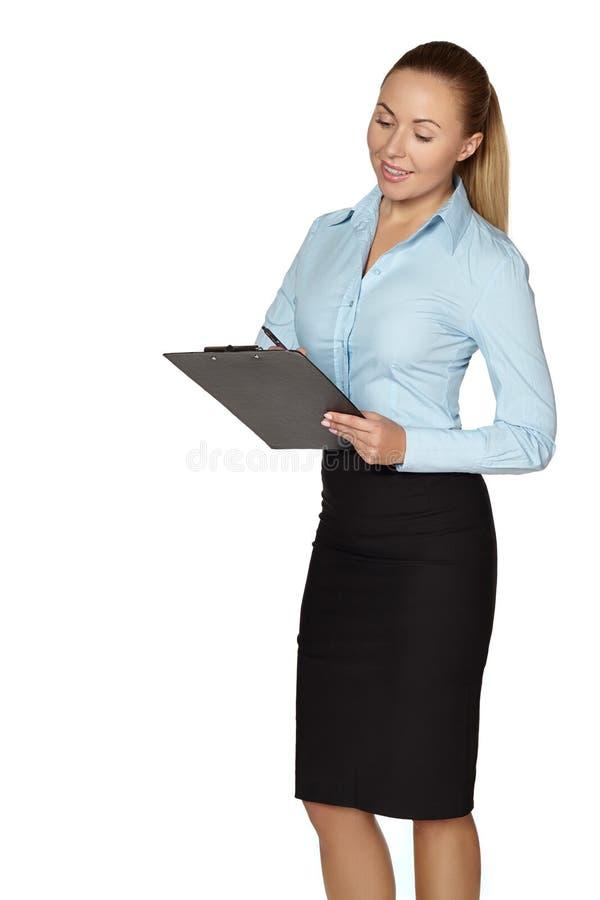 In voller Länge von der lächelnden Frau, die Anmerkungen macht lizenzfreie stockfotografie