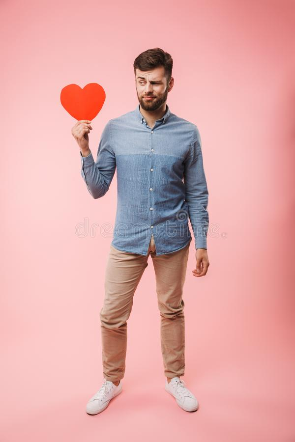 In voller Länge von einem verwirrten jungen Mann, der rotes Herz hält stockfotos