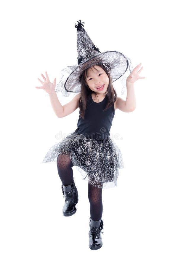 In voller Länge von tragendem Hexenkostüm des kleinen asiatischen Mädchens für hallo stockbild