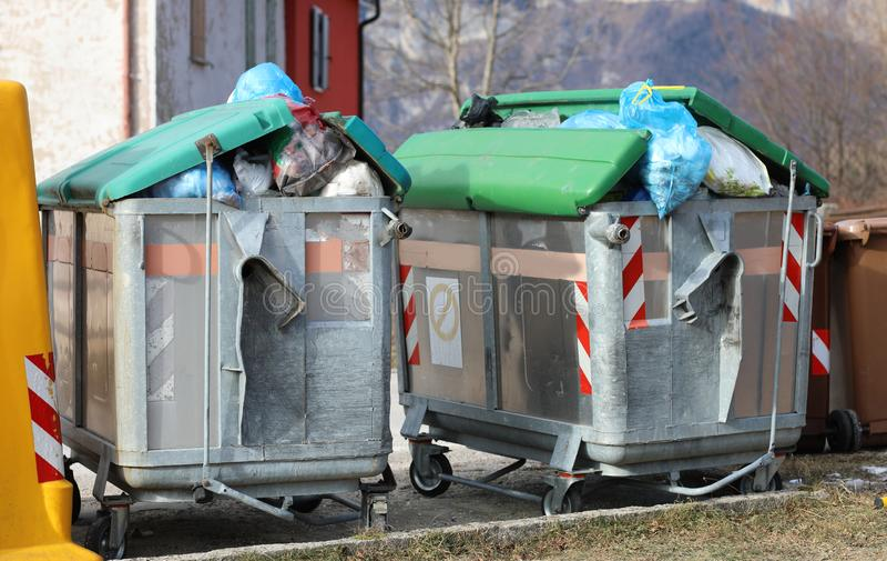 voller Müllcontainer zwei und viele Abfalltaschen auf der Straße stockfotos
