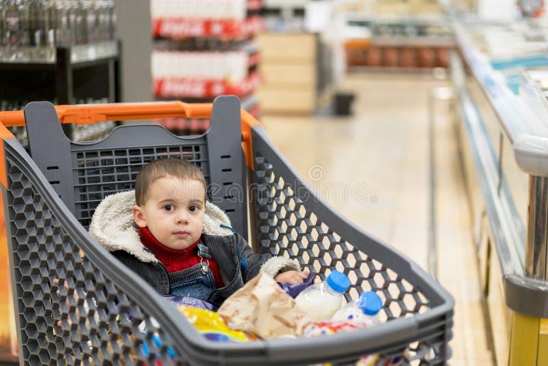 Voller Warenkorb mit Lebensmittel im Supermarkt Im Warenkorb sitzt ein Baby stockbilder