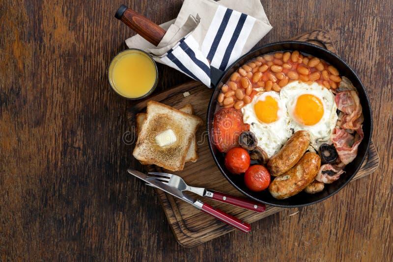 Volles englisches Frühstück mit Orangensaft auf rustikalem hölzernem backgr lizenzfreie stockfotografie