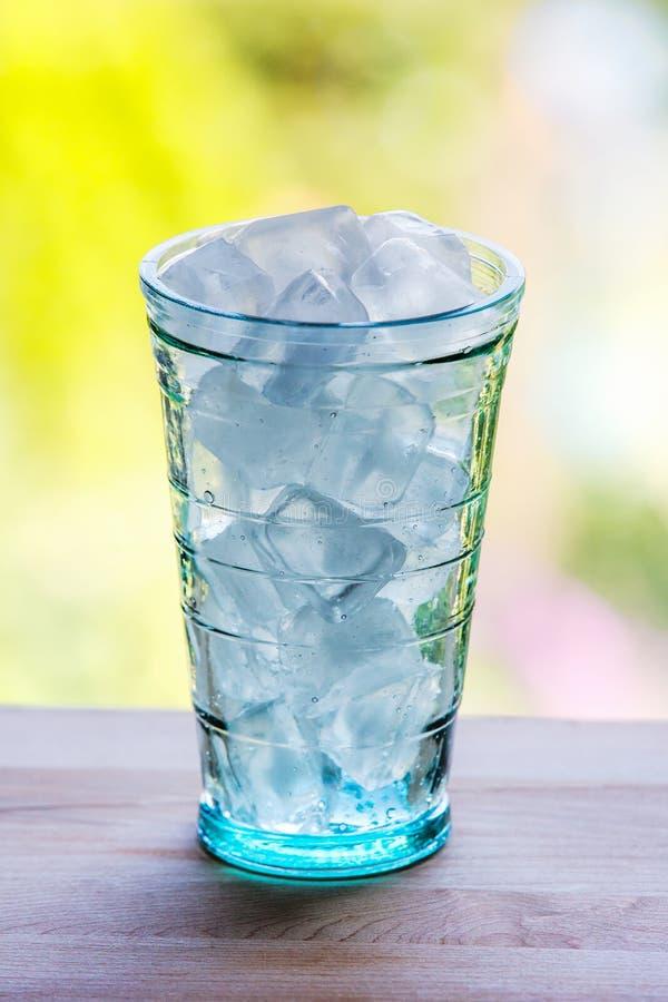 Volles Glas Wasser mit Eis auf der hölzernen Küchenarbeitsplatte lizenzfreies stockfoto
