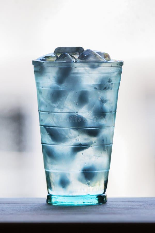Volles Glas Wasser mit Eis auf der hölzernen Küchenarbeitsplatte brig stockfoto