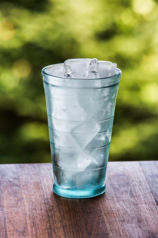Volles Glas Wasser mit Eis auf der hölzernen Küchenarbeitsplatte Wodd lizenzfreie stockfotos