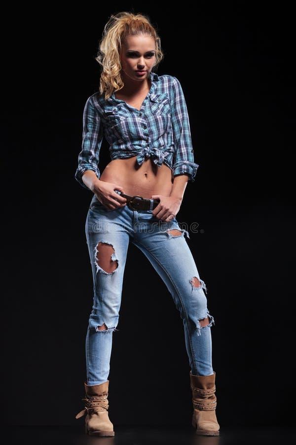 Volles Körperbild einer heißen jungen Frau im Jeanshemd und -stiefeln stockfotografie