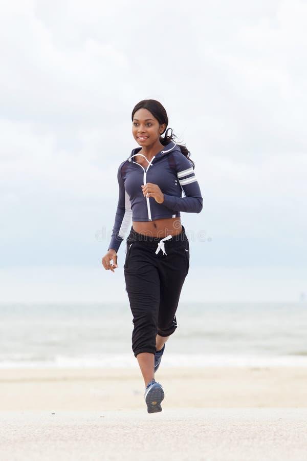 Volles Körperporträt der gesunden jungen schwarzen Frau, die am Strand läuft lizenzfreie stockfotos