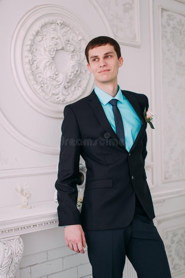 Volles Körperporträt des jungen stilvollen Geschäftsmannes in der Bindung und Weste mit den Händen auf Taille stockbild