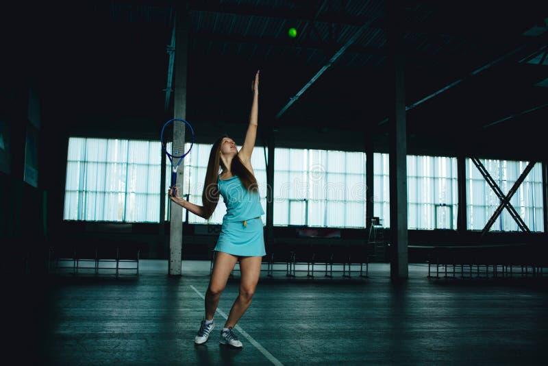 Volles Körperporträt des Tennisspielers des jungen Mädchens in der Aktion in einem Tennisplatz Innen lizenzfreies stockbild