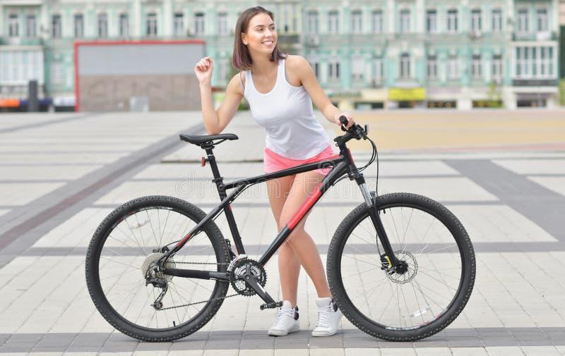Volles Körperporträt einer schönen stilvollen Frau draußen gekleidet in weißer T-Shirt Stellung mit Fahrrad stockfoto