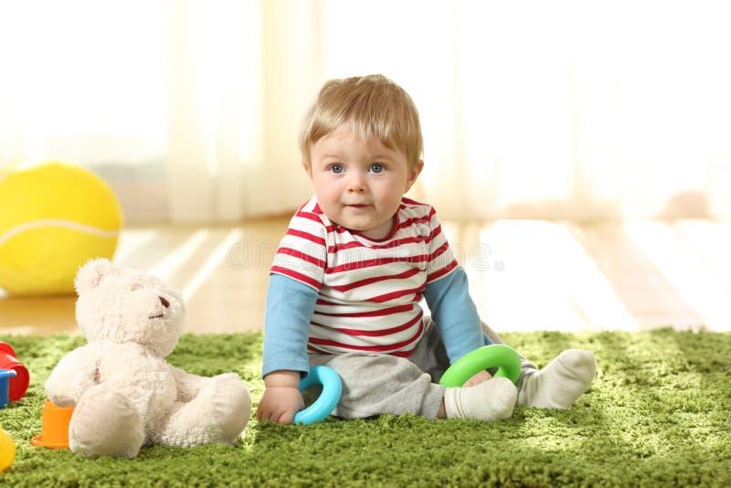 Volles Körperporträt eines einzelnen Kindes, das auf dem Boden sitzt stockfotografie