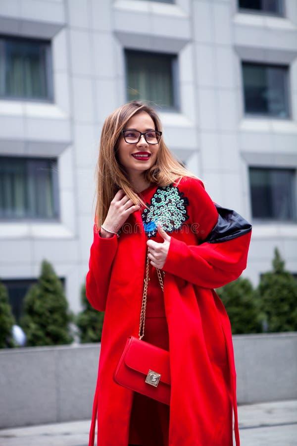 Volles Körperporträt im Freien der jungen schönen modernen Frau, die in Mantelholding der Straße vorbildliche tragende rote modis stockbild
