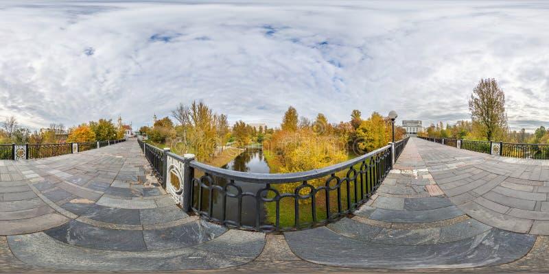 Volles nahtloses kugelförmiges Würfelpanorama 360 Grad Winkelsicht über Fußgängerbrücke über kleinem Fluss im Herbststadtpark her lizenzfreie stockfotos