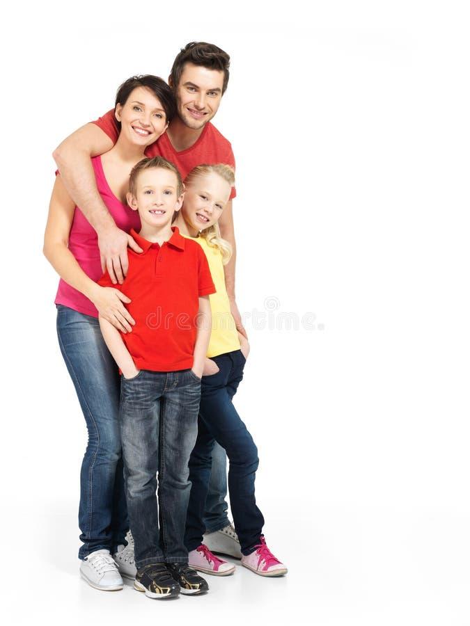 Volles Porträt der glücklichen jungen Familie mit zwei Kindern lizenzfreies stockbild