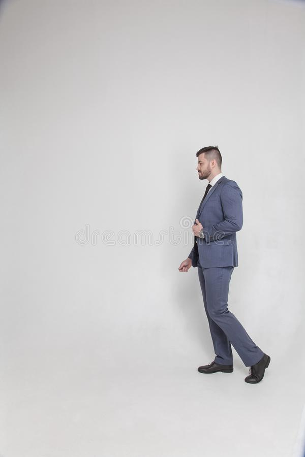 Volles Porträt eines Geschäftsmannes, der auf einen weißen Hintergrund geht Linker Raum für Ihr Logo oder Text lizenzfreie stockfotografie