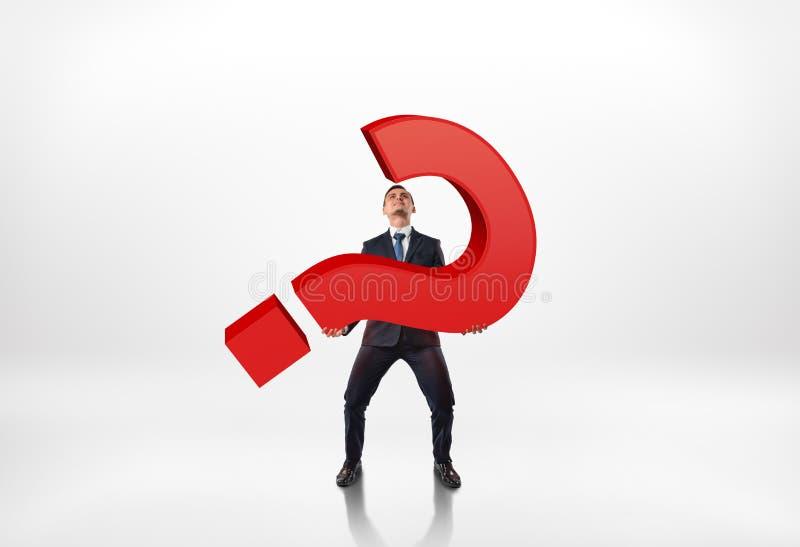 Volles Porträt eines Geschäftsmannes, der großes Fragezeichen des Rotes 3d lokalisiert auf weißem Hintergrund hält stockfotografie