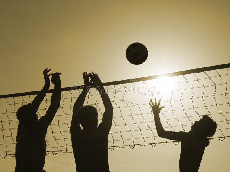 Volley-ball. Silhouettes of three men playing beach volleyball