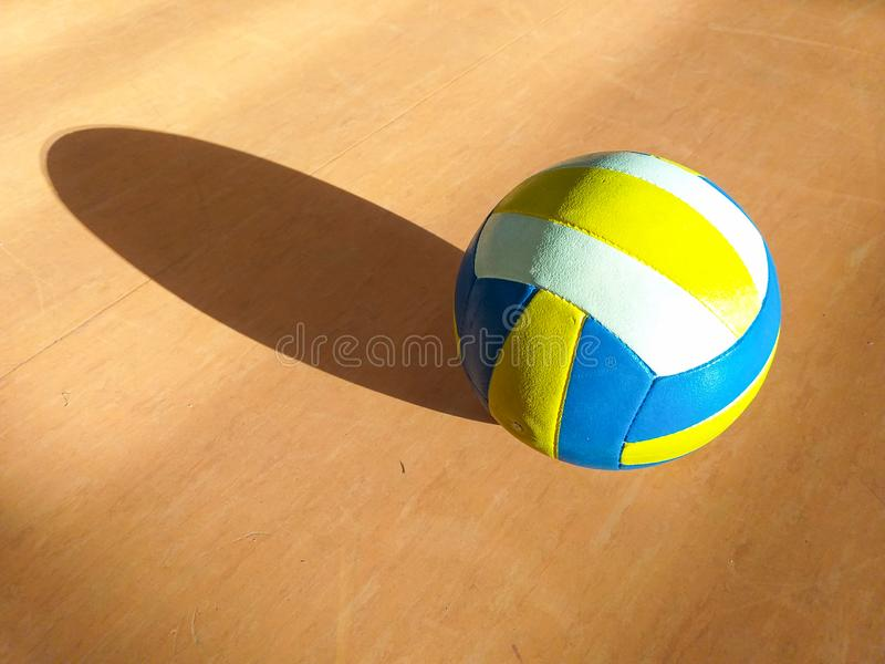 a volley ball in yellow, blue and red colors on the wooden floor of the basketball court projecting its own shadow on the stock photo