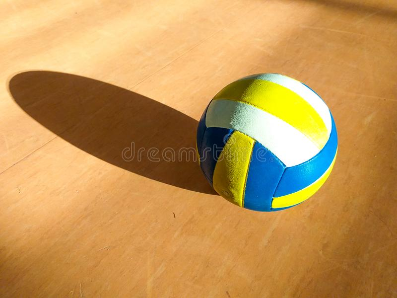 A volley ball in yellow, blue and red colors on the wooden floor of the basketball court projecting its own shadow on the. Close up of a leather volley ball in royalty free stock image