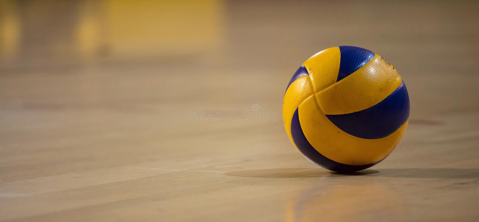 Volleyball ball on blurred wooden parquet background. Banner, space for text, close up view with details. stock photography
