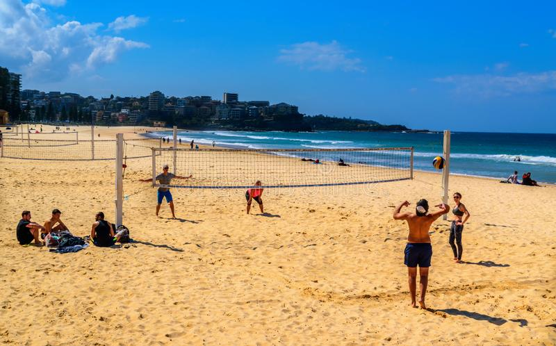 Volleyball at the beach in Manly, Australia and ocean in the background. Two couples are playing volleyball at the beach in Manly, Australia. Manly beach is stock image