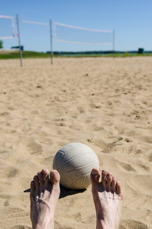 Volleyball de plage avec le ciel bleu et le filet et les pieds photo libre de droits