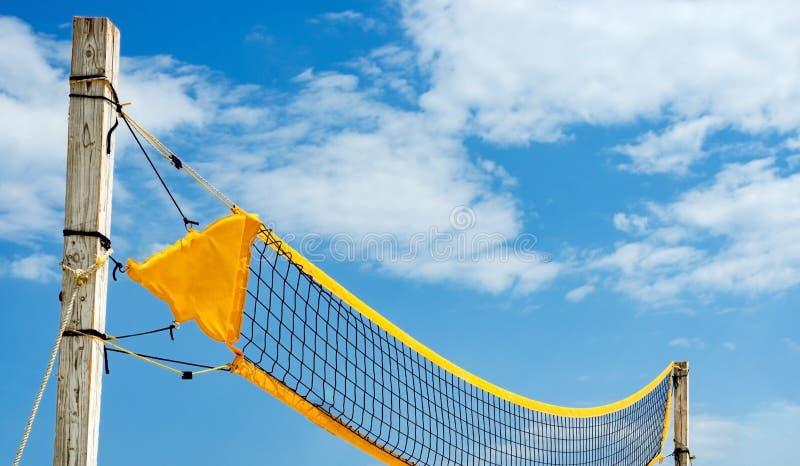 Volleyball de plage jaune de filet contre le ciel bleu Activités de détente des vacances à la mer photos stock