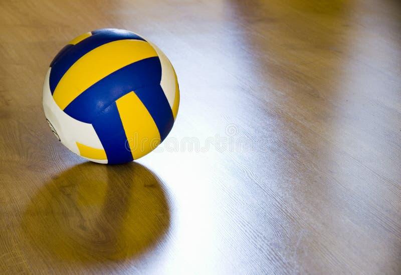 Volleyball on hardwood floor stock image