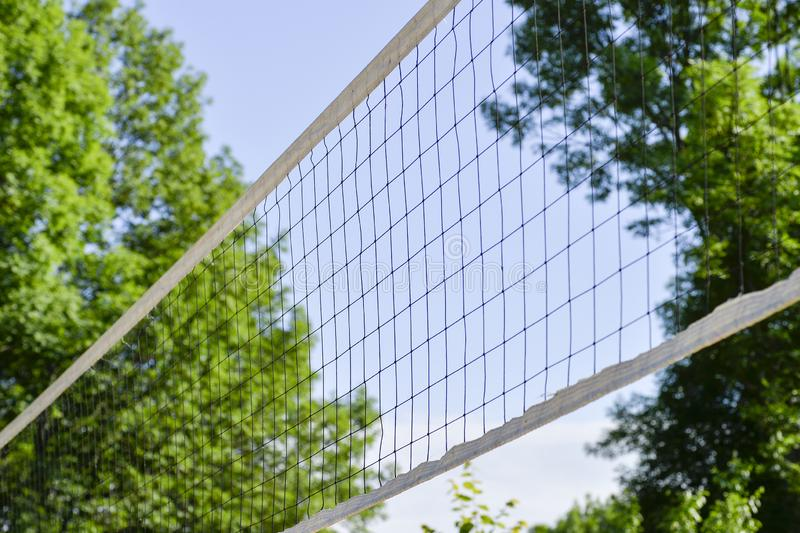 Volleyball net diagonally on the background of the sky and the crowns of trees. Background royalty free stock photos
