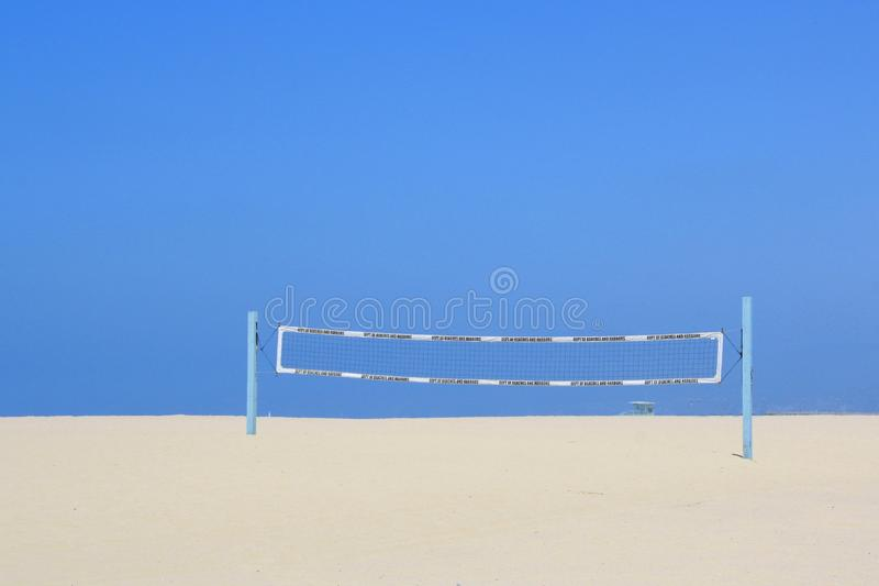 Volleyball net on a sandy beach under a blue sky stock photography