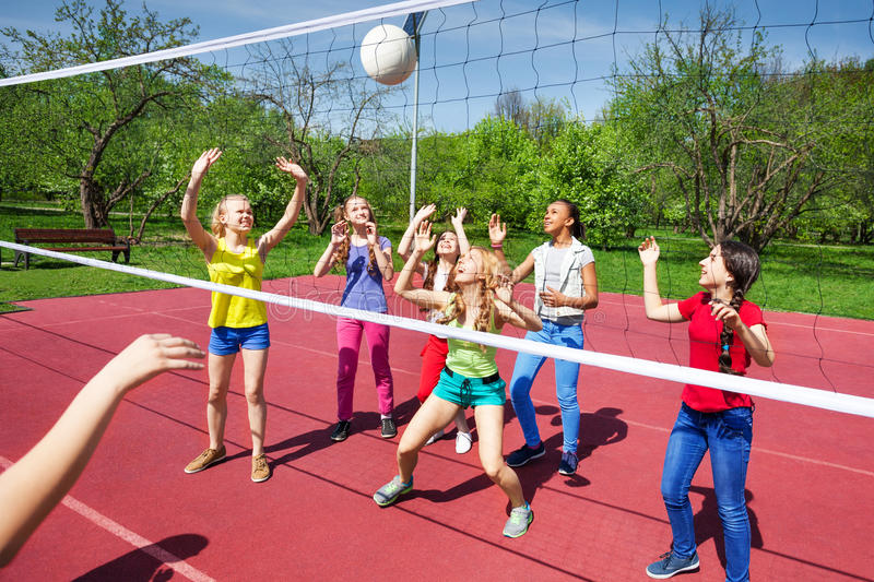 Volleyball net view on girls trying to catch ball stock photo