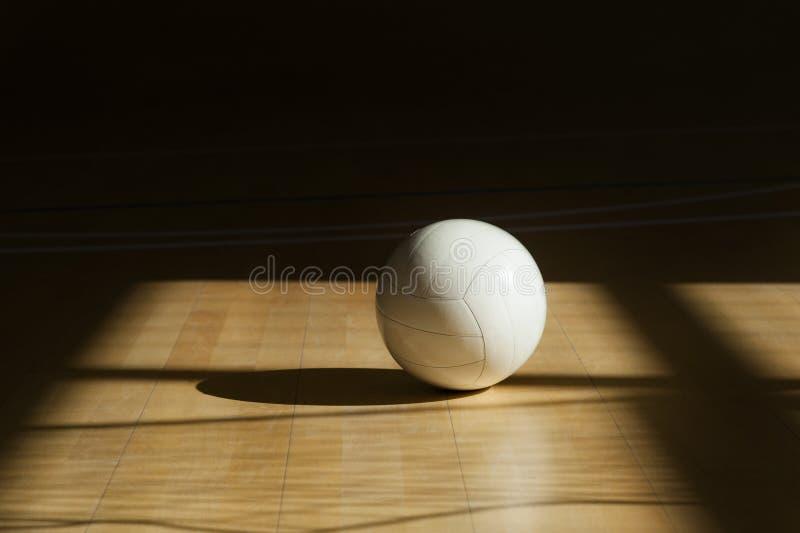 Volleyball sur le parquet avec le fond noir photo stock